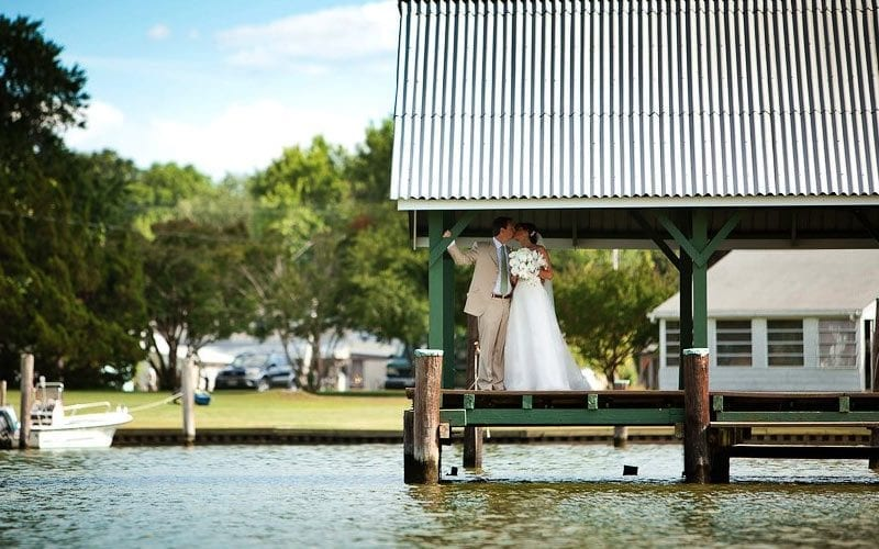 The Oaks Waterfront Inn & Events Maryland Wedding Venues newlyweds kissing on dock on waterfront