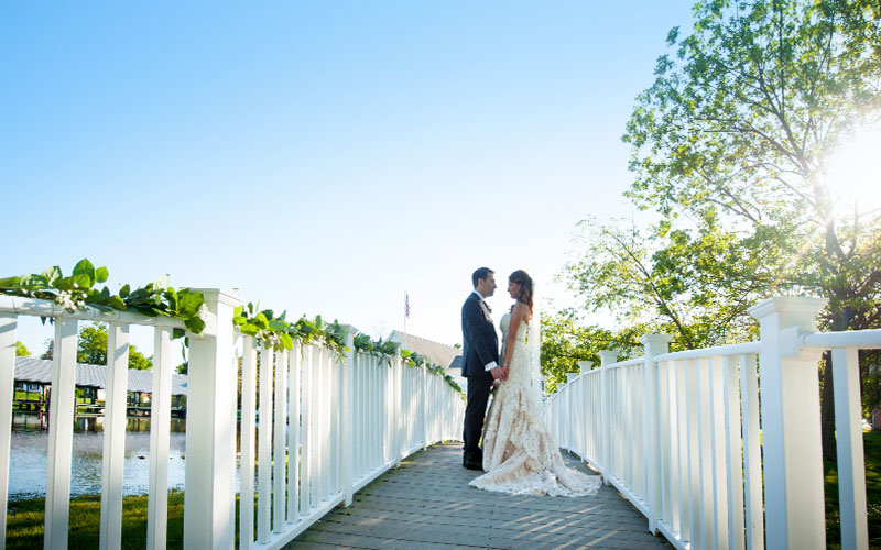 The Oaks Waterfront Inn & Events Maryland Wedding Venues newlyweds share quiet moment on bridge