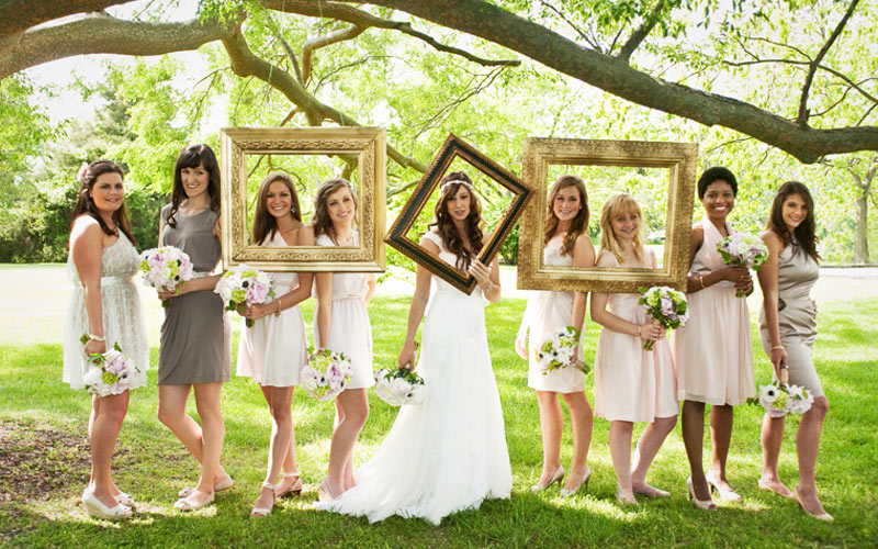 bridal party posing with picture frames for bohemian wedding
