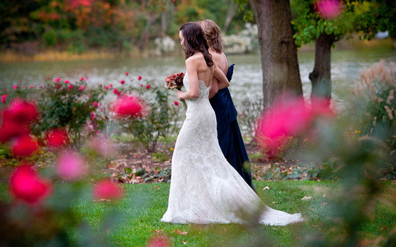 The Oaks Waterfront Inn & Events Maryland Wedding Venues bride walking with bridesmaid on waterfront