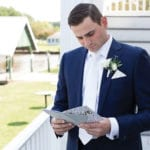 The Oaks Waterfront Inn & Events Maryland Wedding Venues groom on waterfront reading wedding invitation