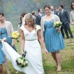 The Oaks Waterfront Inn & Events Maryland Wedding Venues bridesmaid following bride with train on waterfront