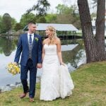 The Oaks Waterfront Inn & Events Maryland Wedding Venues newlyweds hold hands and walk on waterfront