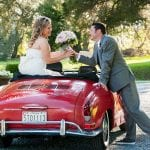The Oaks Waterfront Inn & Events Maryland Wedding Venues newlyweds kissing on wedding theme roadster
