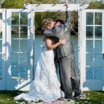The Oaks Waterfront Inn & Events Maryland Wedding Venues newlyweds kissing after nuptials on waterfront