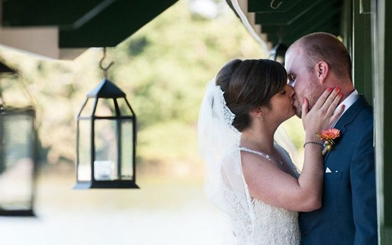 The Oaks Waterfront Inn & Events Maryland Wedding Venues bride kisses groom outside rustic wedding venue