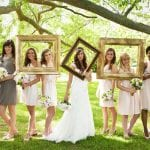 The Oaks Waterfront Inn & Events Maryland Wedding Venues bridal party posing with picture frames for bohemian wedding