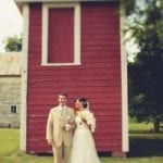 The Oaks Waterfront Inn & Events Maryland Wedding Venues newlyweds pose in front of rustic outdoor barn wedding reception