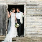 The Oaks Waterfront Inn & Events Maryland Wedding Venues newlywed couple standing in rustic wedding venue