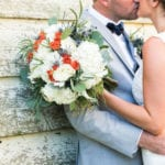 The Oaks Waterfront Inn & Events brides and groom kissing outside rustic wedding venue in maryland