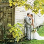 The Oaks Waterfront Inn & Events Maryland Wedding Venues bride and groom kissing outside rustic wedding venue
